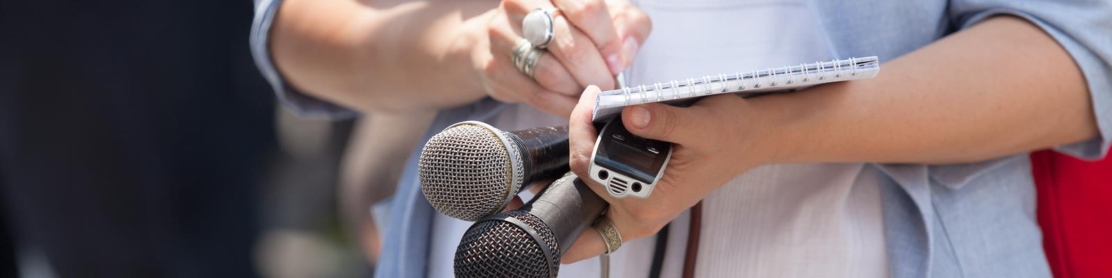 Close up of journalist holding microphone and note book while taking notes