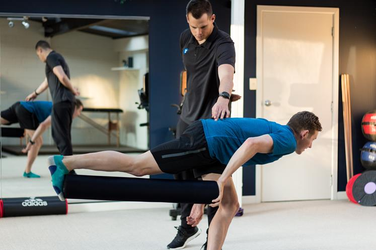 Luke Taylor demonstrating exercise technique with client