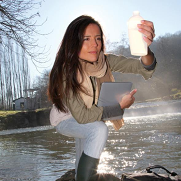 Scientist looking at water quality in a stream