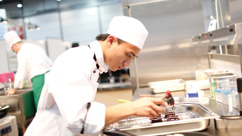 Culinary arts student preparing food in Wintec kitchens