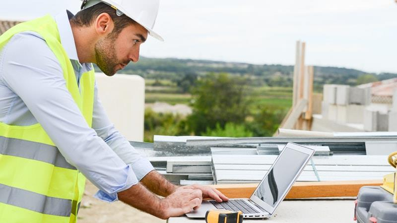 Quantity surveyor examining content on a laptop