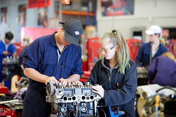 Trades students working on car engine