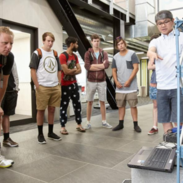 Students looking at demonstration of equipment by tutor