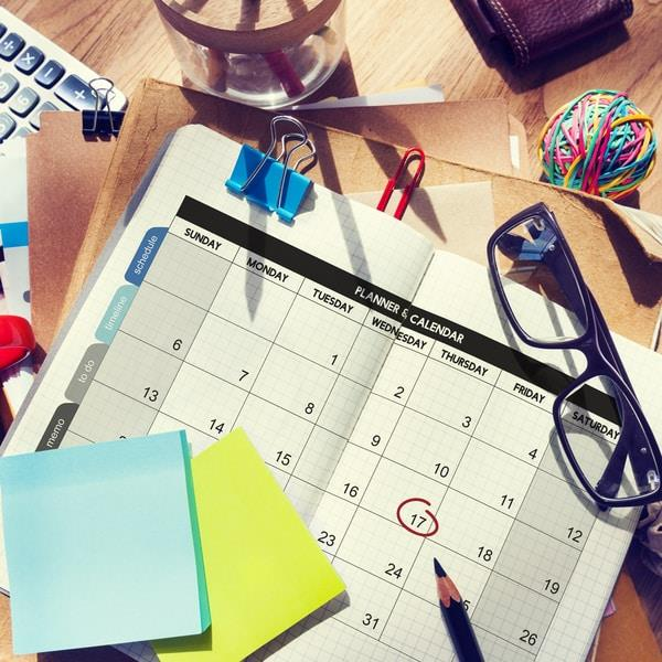 A calendar with a date circled surrounded by office equipment
