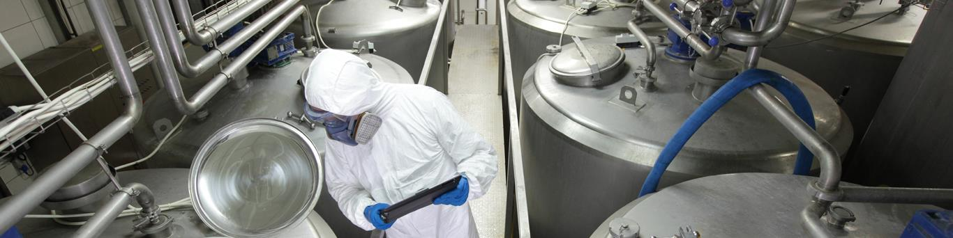 Dairy process worker checking milk quality in a factory