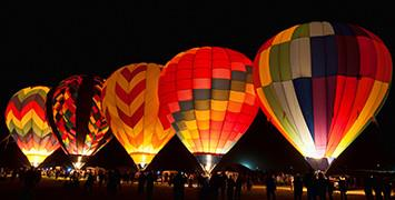 Hot air balloons lit up against the night sky