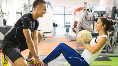 Personal trainer helping client undertake sit-ups in a gym