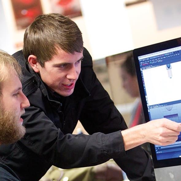 Art and design tutor demonstrating technique on a mac to student