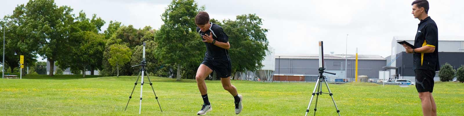sports scientist measuring athlete speed during run