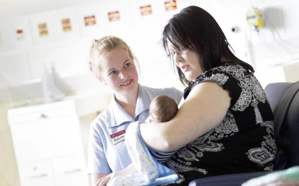Midwifery student on placement talking to patient with baby