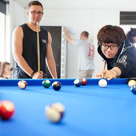 Students playing pool in recreation room of village accommodation