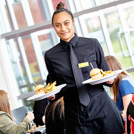 Student waiter carrying food to table