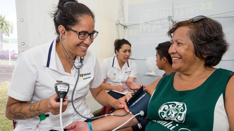 Nursing student taking blood pressure of client