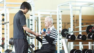 Waikato Human Performance Hub student assisting older man with exercise technique