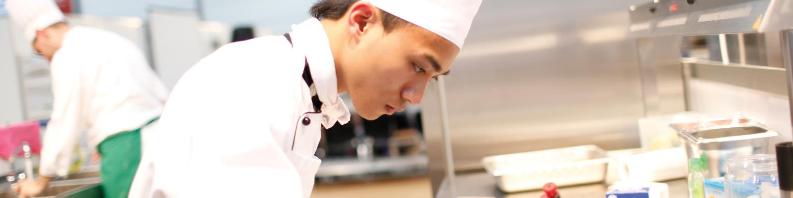 Cookery student/chef preparing food in kitchens