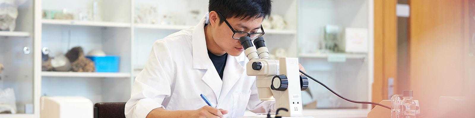 Science student examining item in microscope in a lab