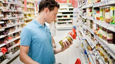 Man reading label on the back of a tin of food in a supermarket