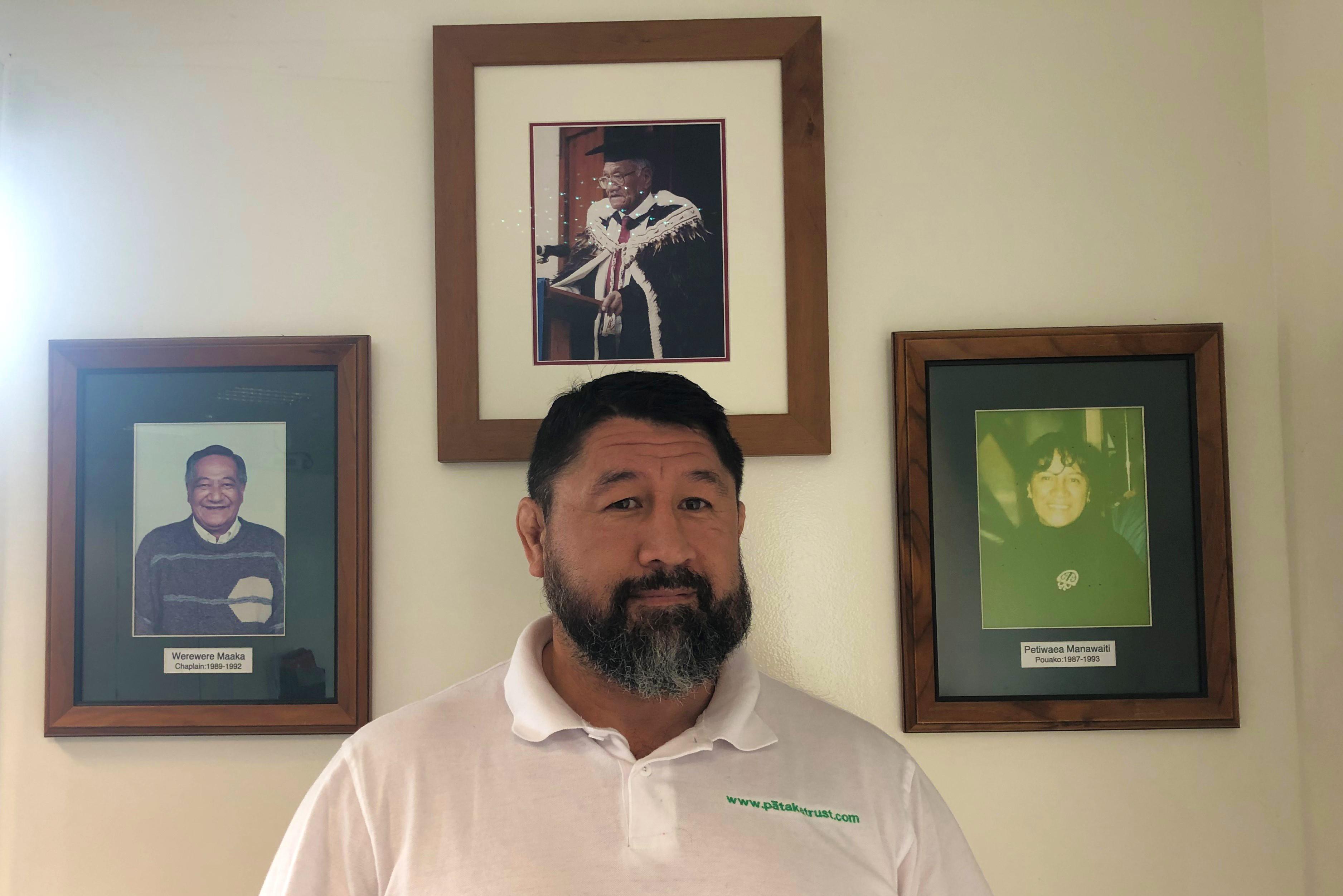 Eady stands next to the image of his nana Petiwaea Manawaiti at Te Kōpū Mānia o Kirikiriroa